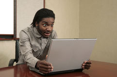 Unhappy man looking at a laptop Royalty Free Stock Image