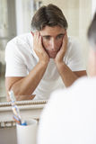 Unhappy Man Looking At Reflection In Bathroom Mirror stock photos