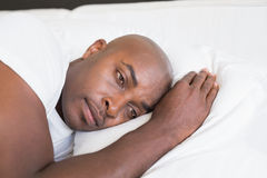 Unhappy man lying in bed Stock Photo
