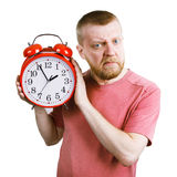 Unhappy man with a red alarm clock in his hand Stock Photography