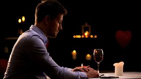 Unhappy man sitting alone in restaurant, waiting for woman, unsuccessful date stock photos