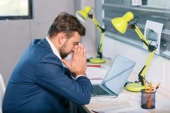 An unhappy man, sitting at the desk in the office, with a frustrated gaze and clings to his face. Indoors. Stock Images