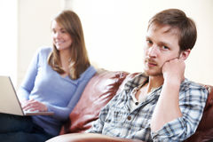 Unhappy Man Sitting On Sofa As Partner Uses Computer Royalty Free Stock Images