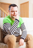 Unhappy man. Sitting on sofa at home stock image