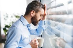 An unhappy man by the window holding a cup of coffee. An unhappy man standing by the window, holding a cup of coffee Stock Photography