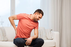Unhappy man suffering from backache at home Stock Images