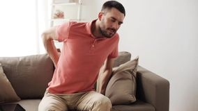 Unhappy man suffering from backache at home. People, healthcare and problem concept - unhappy man suffering from pain in back or reins at home stock footage