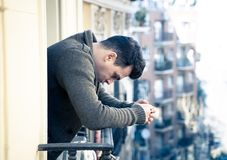 Unhappy man suffering from depression feeling desperate, and worthless on home balcony