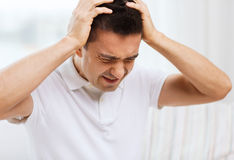 Unhappy man suffering from head ache at home Royalty Free Stock Photos