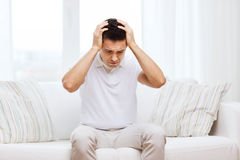 Unhappy man suffering from head ache at home Royalty Free Stock Image