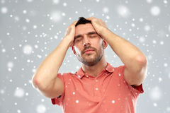 Unhappy man suffering from head ache over snow Stock Images