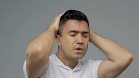 Unhappy man suffering from head ache stock video