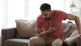 Unhappy man suffering from heart ache at home stock video