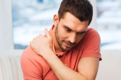Unhappy man suffering from neck pain at home Royalty Free Stock Image
