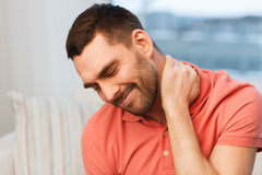 Unhappy man suffering from neck pain at home Stock Image