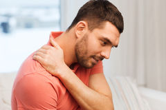 Unhappy man suffering from neck pain at home Royalty Free Stock Photos