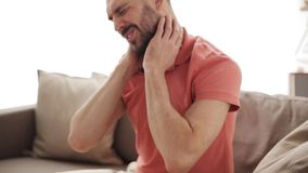 Unhappy man suffering from neck pain at home. People, healthcare and problem concept - unhappy man suffering from pain massaging neck at home stock footage