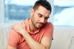 Unhappy man suffering from neck pain at home Stock Images