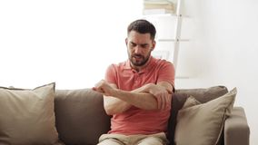 Unhappy man suffering from pain in hand at home. People, healthcare and problem concept - unhappy man suffering from pain in hand at home stock footage