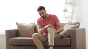Unhappy man suffering from pain in leg at home. People, healthcare and problem concept - unhappy man suffering from pain in leg at home stock footage