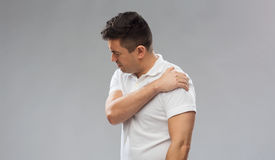 Unhappy man suffering from pain in shoulder Royalty Free Stock Photo
