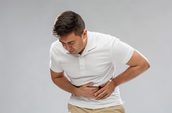 Unhappy man suffering from stomach ache Stock Photos