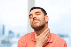 Unhappy man suffering from throat pain at home Royalty Free Stock Photo