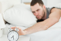 Unhappy man switching off his alarm clock Royalty Free Stock Photography