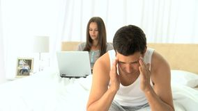 Unhappy man thinking while his wife is working on the laptop. On the bed stock video