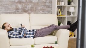 Unhappy man watching tv laid down on sofa