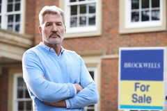 Unhappy Mature Man Forced To Sell Home Through Financial Problems. Mature Man Forced To Sell Home Through Financial Problems Stock Photography