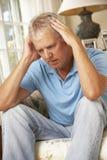 Unhappy Mature Man Sitting On Sofa At Home Stock Photos