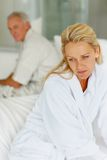 Unhappy mature woman with husband at the back Royalty Free Stock Photo