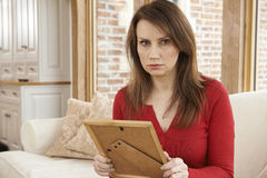 Unhappy Mature Woman Looking At Photograph In Frame Royalty Free Stock Image