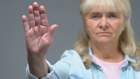 Unhappy mature woman showing stop sign, warning gesture, negative reaction. Stock footage stock footage