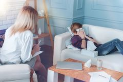 Scared child crying while talking with psychotherapist. Unhappy memories. Teenage girl lying on a sofa getting emotional and wiping his eyes with napkins while Royalty Free Stock Photo
