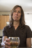 Unhappy Middle Aged Woman in the Kitchen Drinking Wine Royalty Free Stock Image