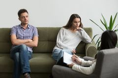 Unhappy millennial couple sitting apart on couch visiting female stock images