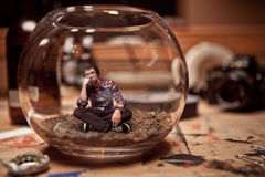 Unhappy Miniature man trapped inside a fishbowl. Unhappy Miniature Waiting Man Trapped inside a Fishbowl Royalty Free Stock Photos