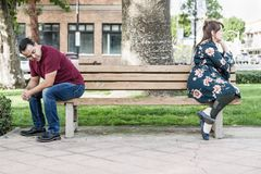Unhappy Mixed Race Couple Sitting Facing Away From Each Other on Park Bench stock image