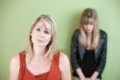 Unhappy Mom. Unhappy Caucasian mom with sad daughter over green background Royalty Free Stock Photos