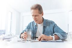 Unhappy moody man looking into a glass. What is it. Unhappy moody suspicious man holding a glass with medicine and looking into it while being suspicious about Stock Photos