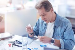 Unhappy moody man looking at his medicine. Will it help me. Unhappy moody pleasant man holding a paper tissue and looking at his medicine while feeling ill Royalty Free Stock Images