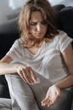 Unhappy moody woman counting pills Stock Images