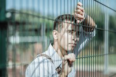 Unhappy musing guy looking forward to meeting. Cannot wait. Attractive unsure guy touching fence and wearing shirt stock photos
