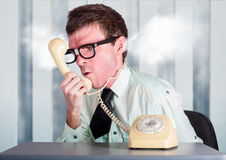 Unhappy nerd businessman yelling down retro phone Royalty Free Stock Images