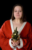 Unhappy New Year. Upset Girl dressed in Santa Claus caftan with fir-tree in hand. Black background Stock Photography
