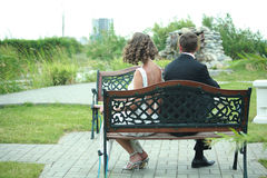 Unhappy newlywed couple. Rear view of unhappy newlywed couple sat back to back on bench outdoors stock photography