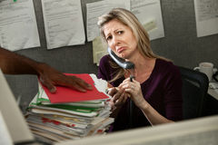 Unhappy Office Woman. Unhappy woman employee given a stack of files stock photography