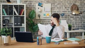 Unhappy office worker reading documents sighing thinking about trouble at work stock video